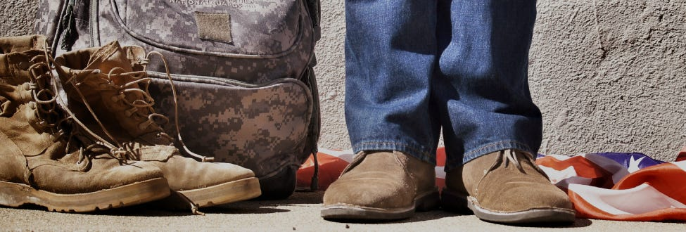 A photo of a person's legs in civilian clothes standing next to a military bag and boots.