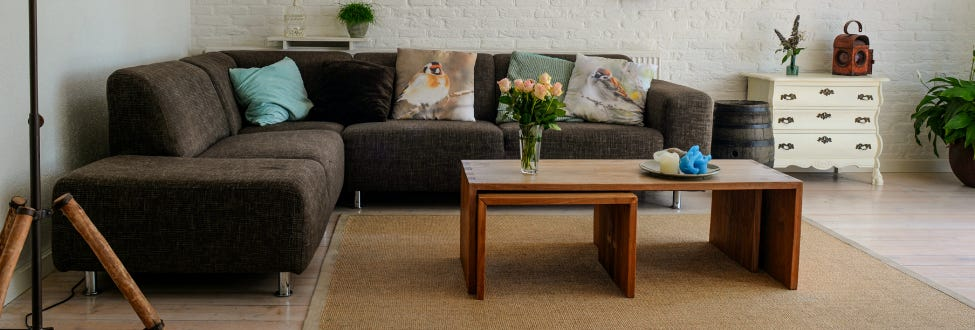A living room with a grey couch, brown coffee table, white brick walls, and plants placed decoratively around the room