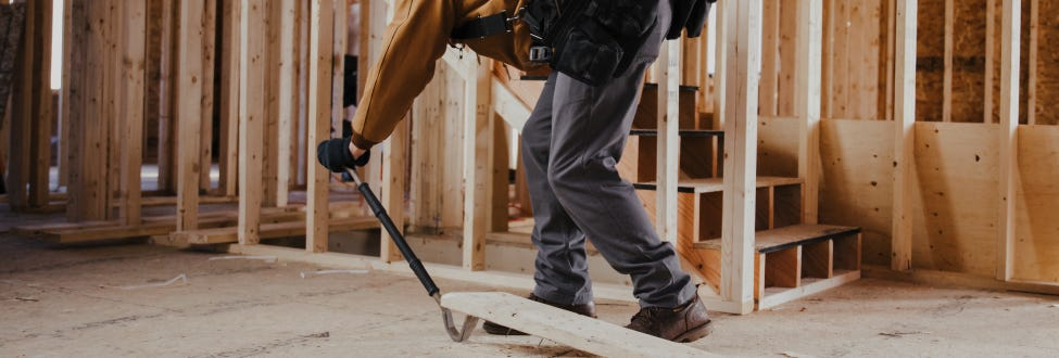 Construction worker using a pry bar on a job site.