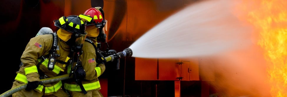 Firefighters fighting fire with hose and water