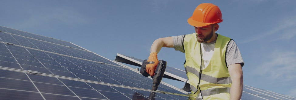 A man in an orange hard hat uses a power drill while installing solar panels on a roof.